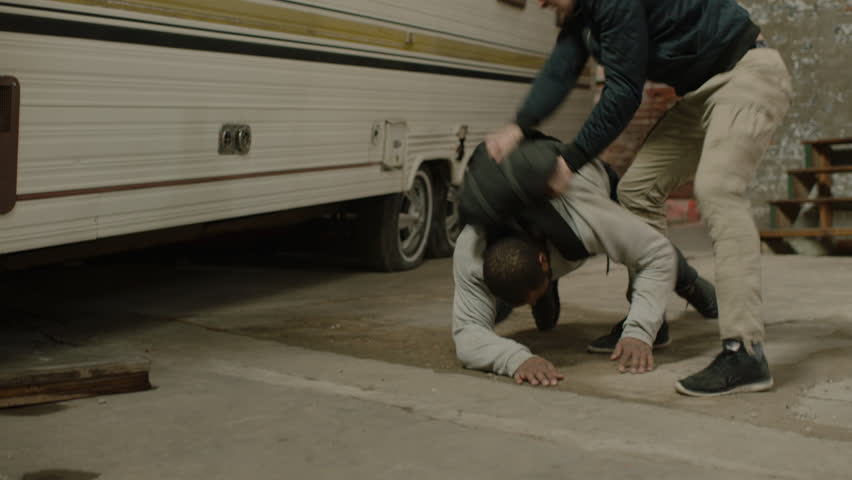 Enraged man fights and tussles with an aggressive man wearing a black backpack, in front of a camper trailer in moody lighting. Medium shot in 4K with an Alexa Mini camera
