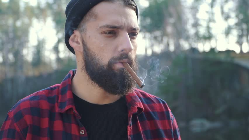Bearded guy smoking brown cigar in the forest near river. A man with a beard in a hat and a plaid shirt smokes a cigar in the autumn forest. #1020843349