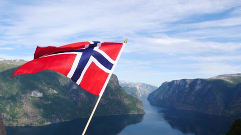 Norwegian flag waving in slow motion against fjord Aurlandsfjord landscape. View from Stegastein viewpoint. National tourist route Aurlandsfjellet