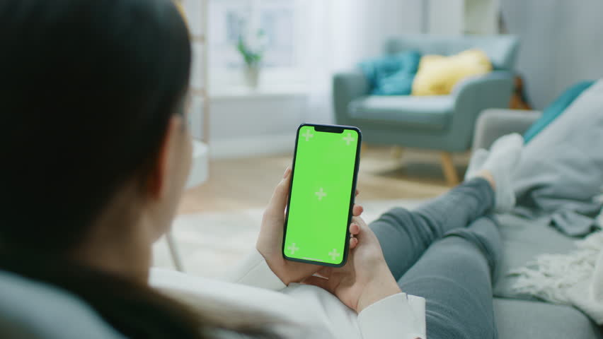 Young Woman at Home Resting on a Couch using with Green Mock-up Screen Smartphone. Girl Using Chroma Key Mobile Phone, Internet Browsing, Posting on Social Networks. Point of View Camera Shot. | Shutterstock HD Video #1020934099