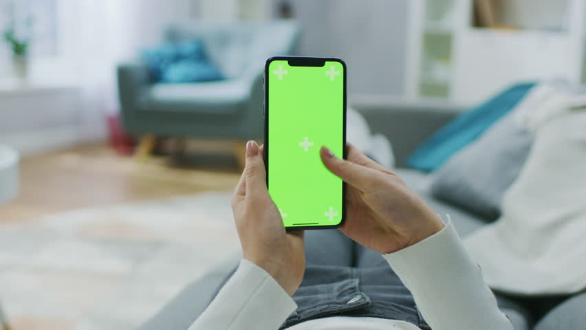 Woman at Home Lying on a Couch using Smartphone with Green Mock-up Screen, Doing Swiping, Scrolling Gestures. Girl Using Mobile Phone, Internet Social Networks Browsing. Point of View Camera Shot. | Shutterstock HD Video #1020934219