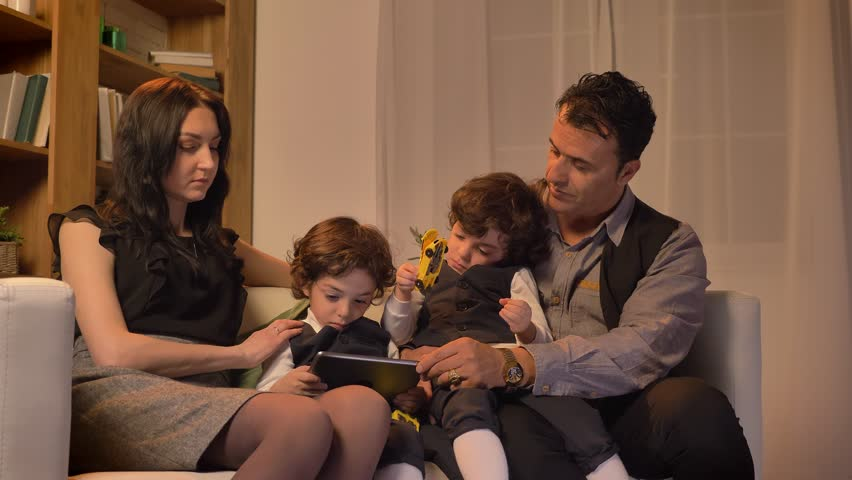 Portrait of arabic perents sitting with their twin sons on couch and watching into tablet in living room in cosy atmosphere. | Shutterstock HD Video #1020962359