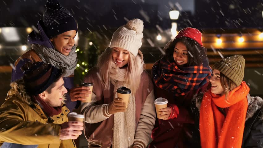 Multiethnic friends in warm clothes drinking coffee and talking in snow street | Shutterstock HD Video #1020990169