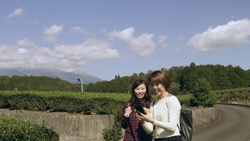 Two excited, happy Japanese women taking pictures together in a tea plantation with Mount Fuji in the background, with soft natural lighting. Wide to Medium shot on 4k RED camera.