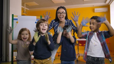 Happy funny multicultural children with smiling teacher showing their hands stained with colorful paint in kindergarten. Portrait of carefree diverse kids with hands in paint posing at art class.