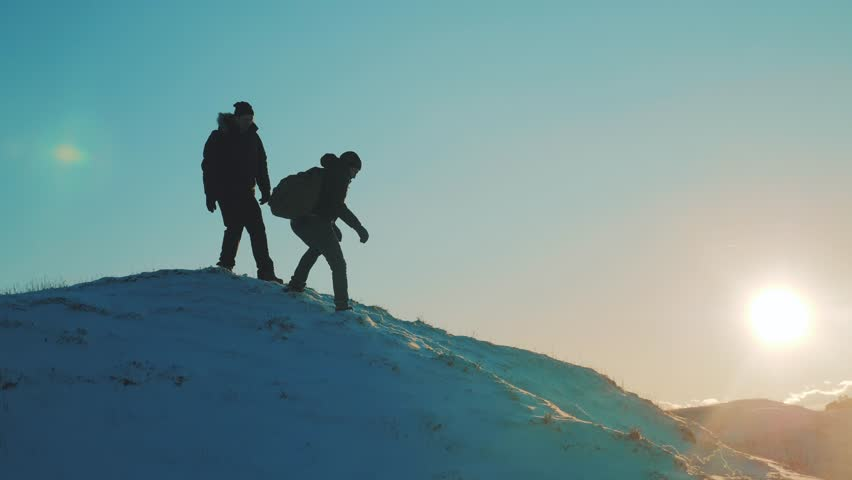 Teamwork silhouette business travel concept. two hikers tourists slips falls come down from climbers climb to the top of the mountain. overcoming hardships the path to victory, teamwork, important | Shutterstock HD Video #1021006219