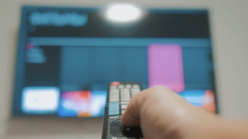 Smart tv with apps and hand. Male hand holding the remote control turn off smart tv . man hand controls TV holding remote. TV concept internet online cinema lifestyle | Shutterstock HD Video #1021006249