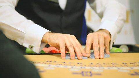 Playing blackjack in casino. Blackjack dealer dealing carts in casino. Men playing blackjack in casino
