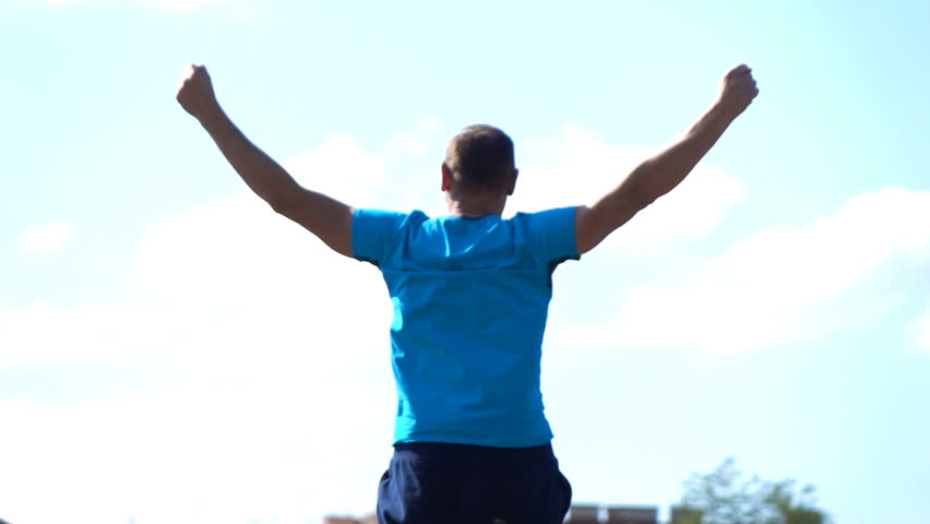 Successful jogger raising arms in the city, super slow motion #1021054879