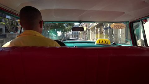 Cuban taxi driver driving 1950's american vintage classic car in old streets of Vieja neighborhood Havana, Cuba