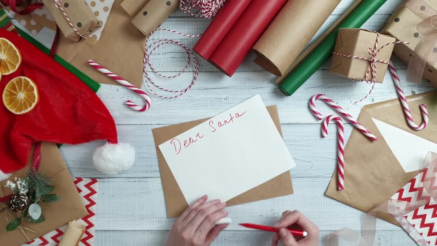 Female teen hand writing a wish list to Santa on wooden table with gifts, wrapping paper, red Christmas decorations. Xmas and Happy New Year composition. Flat lay, top view