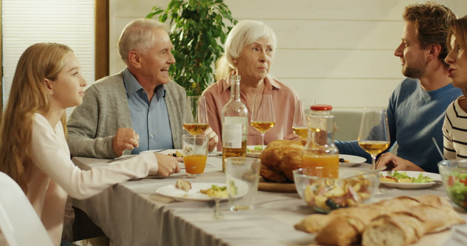 Family dinner of the two kids, their parents and grandparents on a holiday in the cozy living room at home. | Shutterstock HD Video #1021141519