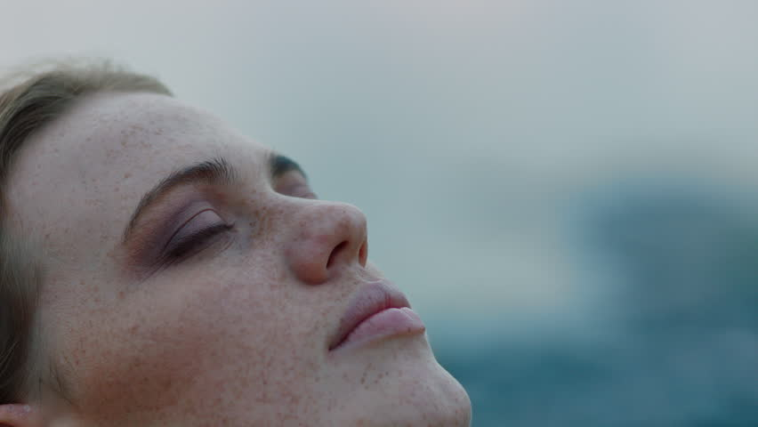 Close up portrait of beautiful young woman looking up praying exploring spirituality contemplating future on cloudy seaside | Shutterstock HD Video #1021159399