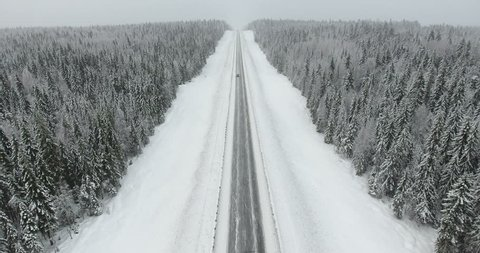 Car driving winter asphalt highway under snowfall and slick condition weather. Straight-line section in north of Russia. Aerial view