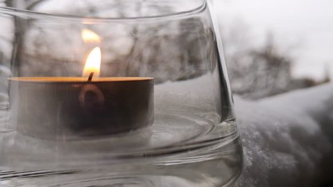 Closeup of a tealight candle in a transparent glass candlestick, which stands in the snow. Background in soft-focus.