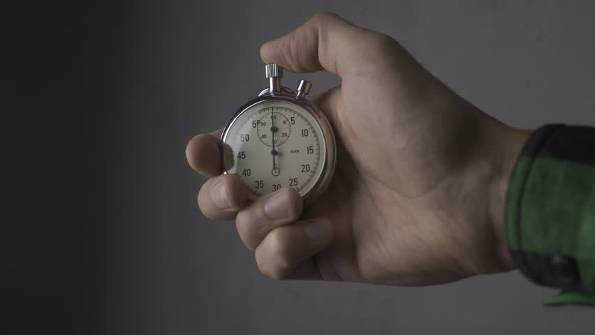 Close-up of one person starting up a stopwatch at grey background. 4K, 10 BIT, 4:2:2. | Shutterstock HD Video #1021289149