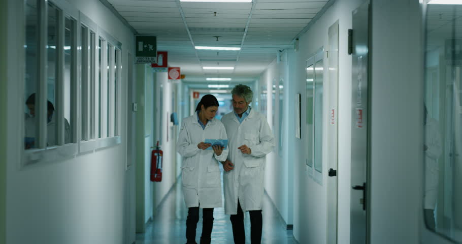 Doctor and nurse discussing the diagnosis of a patient for the future advice for his treatment during walking in a hospital ward. Concept of medicine, technology, health care and people, hospital | Shutterstock HD Video #1021307629