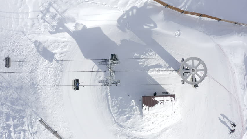 Top view from drone ski lift for transportation skiers and snowboarders on snowy slope. Ski elevator cable way for people transportation on winter mountain in resort. Winter skiing and snowboarding