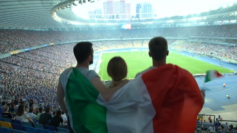 Football fans with Italian flag jumping at stadium, cheering for national team