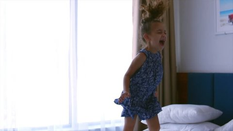 Happy little Caucasian girl jumping on the bed. Slow motion.