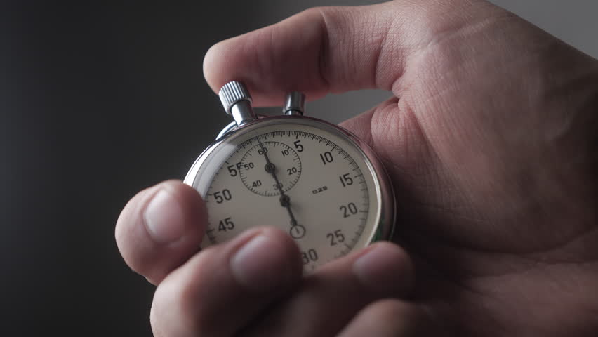 Close-up of one person starting up a stopwatch at grey background. 4K, 10 BIT, 4:2:2. | Shutterstock HD Video #1021336039