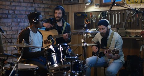 Medium long shot of young musicians rehearsing in garage