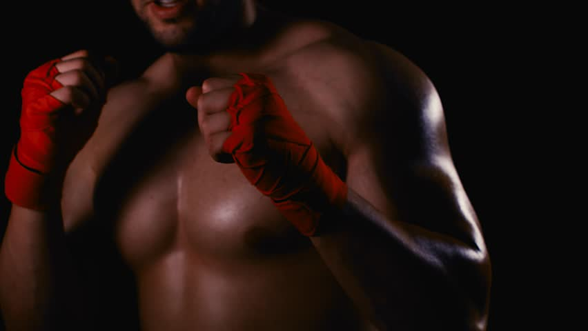 Male boxer with wrapped hands fight training process on black background #1021363339