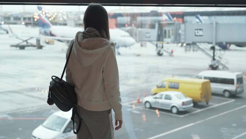 Backside view girl with backpack looks out window at plane and waves her hand. Female standing at window in airport terminal. Concept travel, tour, flight, aircraft, arrivals, lounge, runway, check in #1021366729