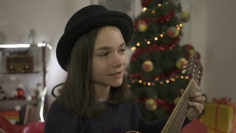 Beautiful young girl playing guitar and singing song, close up. Christmas tree with blink lamps and New Year gifts in background of room. Portrait of female child with hat. Concept music and holidays.