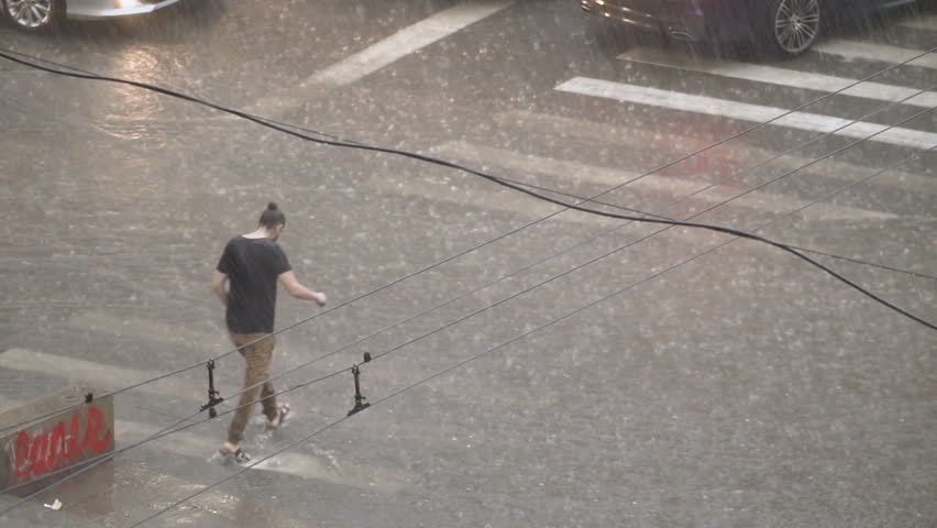 Wet man in the street. The guy walks in heavy rain. Flood disaster after heavy rain. Heavy rain on the streets of the city. Urban disaster. People are trying to escape from the elemental rain. | Shutterstock HD Video #1021423909