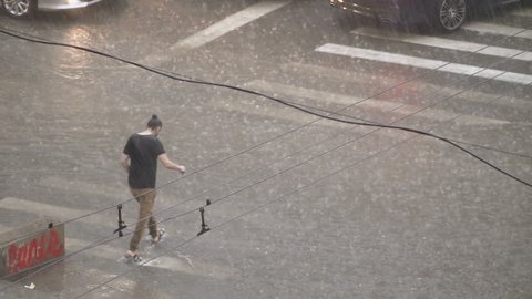 Wet man in the street. The guy walks in heavy rain. Flood disaster after heavy rain. Heavy rain on the streets of the city. Urban disaster. People are trying to escape from the elemental rain.