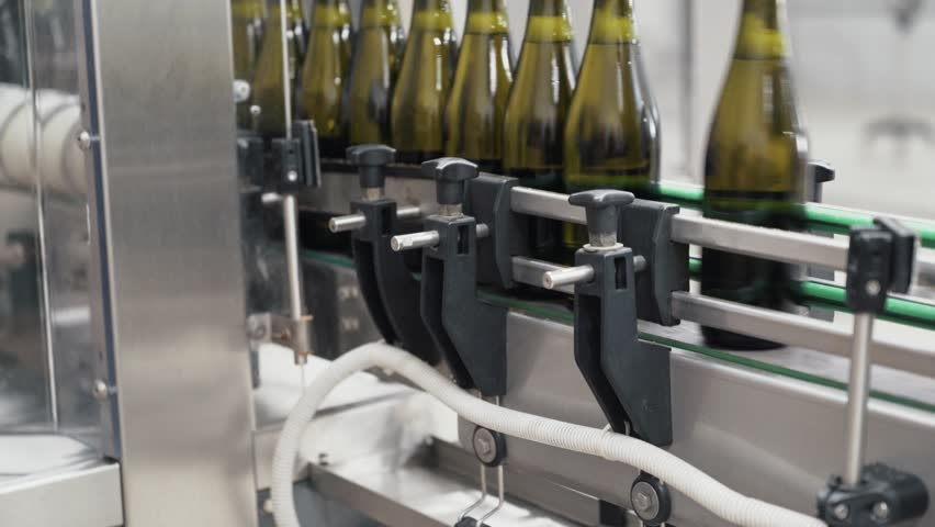 Close-up green color bottles move along conveyor line at a factory of champagne or wine. Production of champagne or wine. Plant for bottling alcoholic beverages | Shutterstock HD Video #1021440859