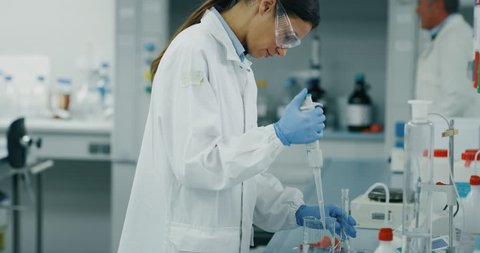Portrait of female scientist with a pipette analyzes a liquid to extract the DNA and molecules in the test tubes in laboratory. Shot in 8K. Concept: research,biochemistry, pharmaceutical medicine