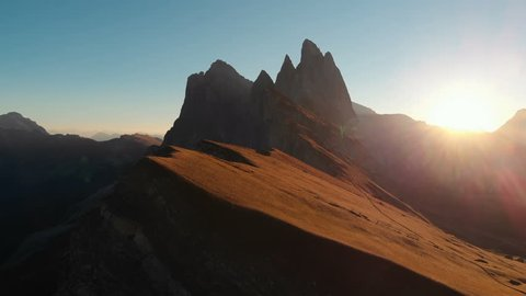 Aerial Drone Footage View on Majestic panorama of beautiful sunset or sunrise in the Italian picturesque resort Seceda dolomite mountains. Beautiful landscape near the edge of world at 4K resolution.