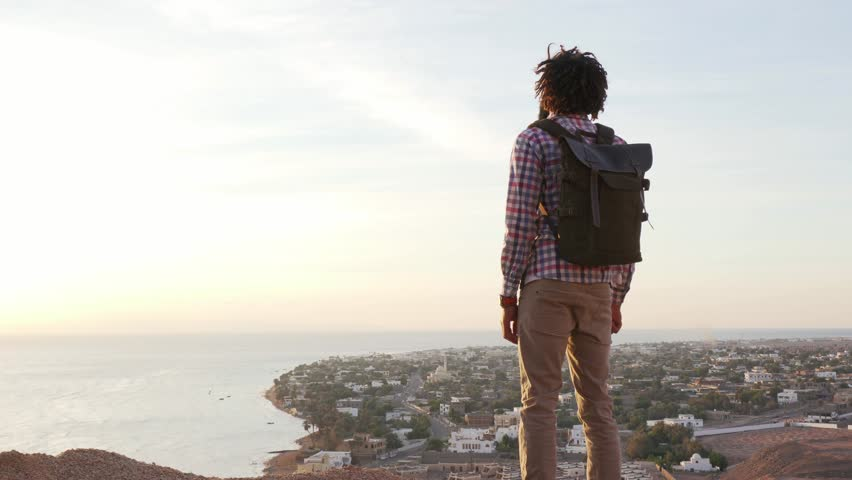 Handsome black male raise his hand in success pose standing on a cliff | Shutterstock HD Video #1021459309