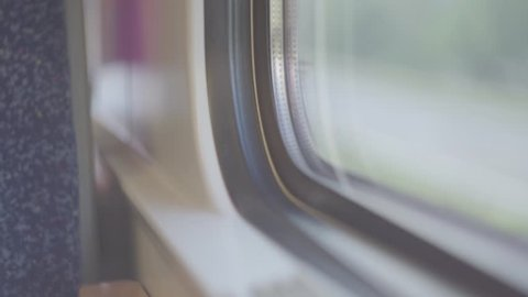 Video of window corner in aing train with blurred outside as cars are passing by