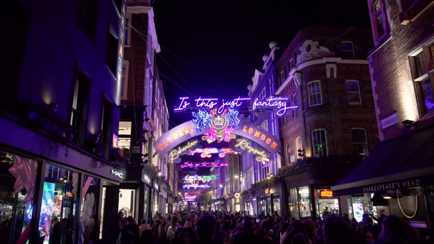 Christmas Lights Neon Street Illumination Crowd Of People Walking Through Carnaby In The Soho District Downtown London City At Night