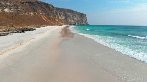 Aerial shot of white sand beach and turquoise ocean water in Oman, near Salalah. Arabian Peninsula.