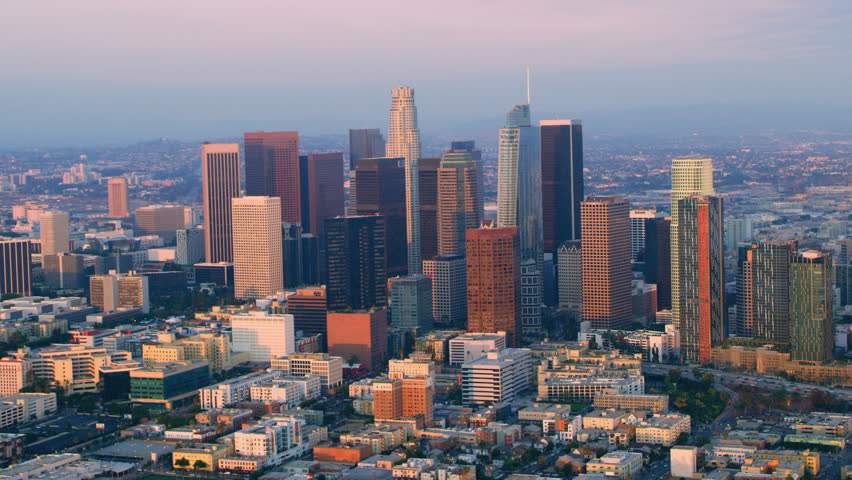 Aerial helicopter shot flying around downtown Los Angeles at sunset. Wide shot filmed with a RED camera.