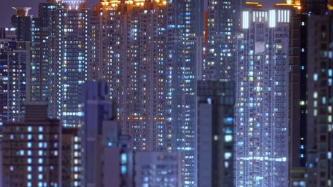 Loop of Hong Kong apartments at night. Chinese crowded city with lights turning on and off at midnight. Fast paced modern Asian night-scape time lapse in urban metropolis.
