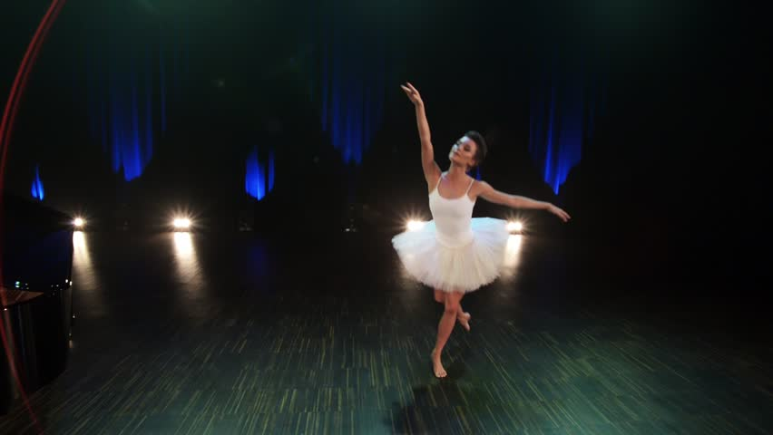 Camera shows beautiful young brunette ballerina wearing elegant white dress enthusiastically dances ballet with bare feet on stage in concert hall with dimmed lighting.   Shutterstock HD Video #1021580779