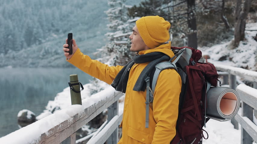 Young traveler man having video chat on winter holiday. Hiker waving at webcam on mobile phone camera sharing his friends winter travel vacation adventure