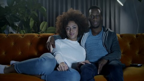 Couple enjoying a cozy night in on the sofa watching tv