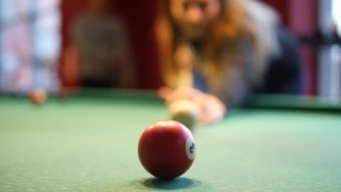 In a billiard club or a night club a women in playing billiard. In the background group of friends is visible. Concept: billiard game, pool, snooker, club, pub, entertainment, women's day