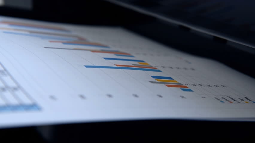 Business Report And Investment Charts Printed On Office Printer. Close Up