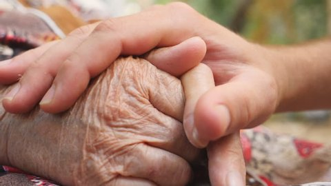 Close up of young male hand comforting an elderly arms of old woman outdoor. Grandson and grandmother spending time together outside. Concept of care and love. Side view Slow motion