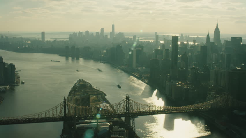 Aerial view of Manhattan skyline skyscrapers from river and the Queensboro Bridge in New York during the day under blue skies. Wide shot on 4K RED camera.