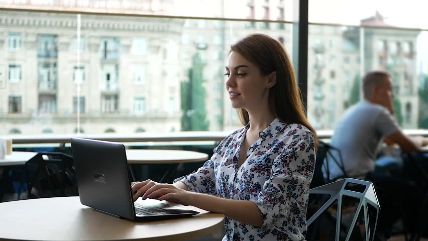 Young charming female freelancer using laptop computer for distance job while sitting in modern coffee shop interior, beautiful Caucasian woman working on net-book during morning breakfast in cafe bar | Shutterstock HD Video #1021781119