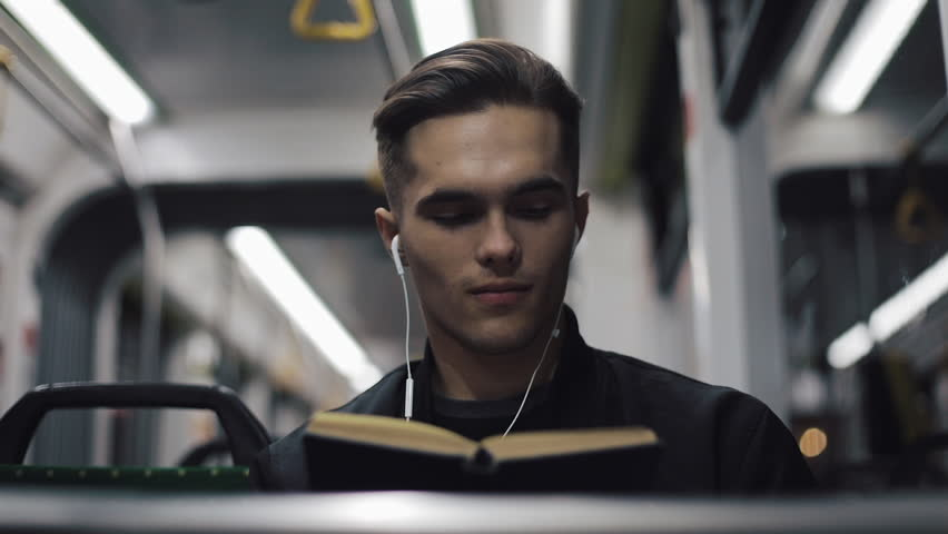Young handsome man sitting on public transport reading a book - commuter, student, knowledge concept. Young man with headphones in the tram reading a book | Shutterstock HD Video #1021803169
