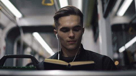 Young handsome man sitting on public transport reading a book - commuter, student, knowledge concept. Young man with headphones in the tram reading a book